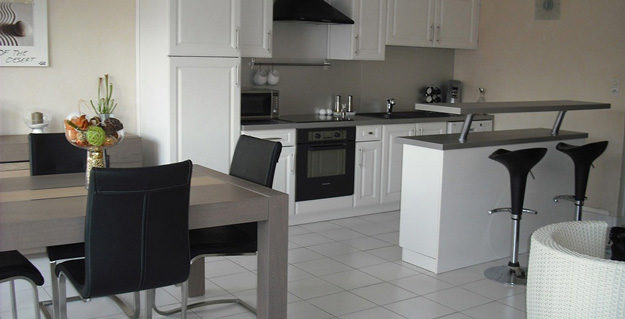 White and grey kitchen with counter and table