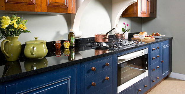 Black kitchen counter with dark blue cabinet fronts